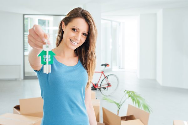 Beautiful smiling woman holding house keys of her new house, real estate and relocation concept