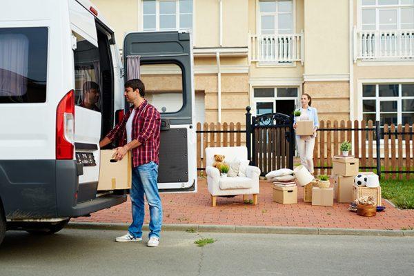 Young man putting carton box into van