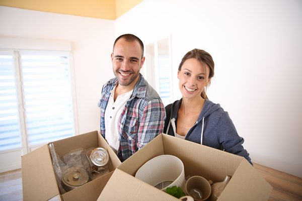 Cheerful young adults packing their stuff in cardboards