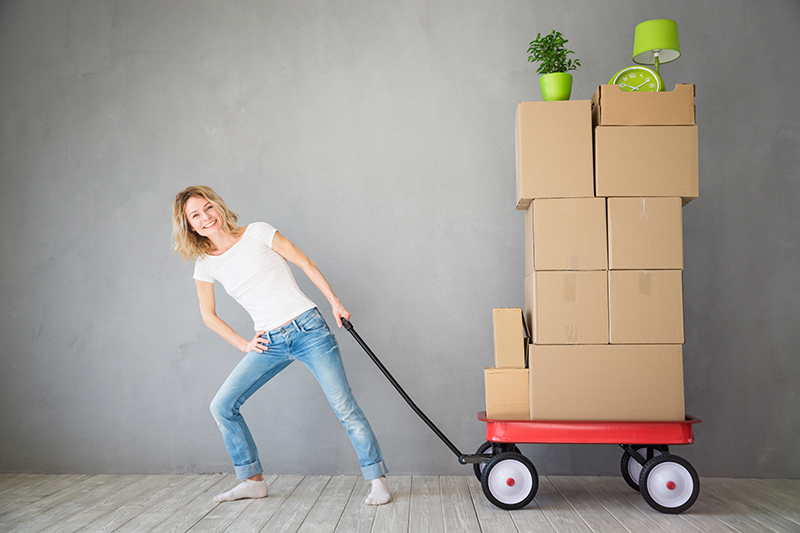 Happy woman playing into new home. Moving house day and express delivery concept