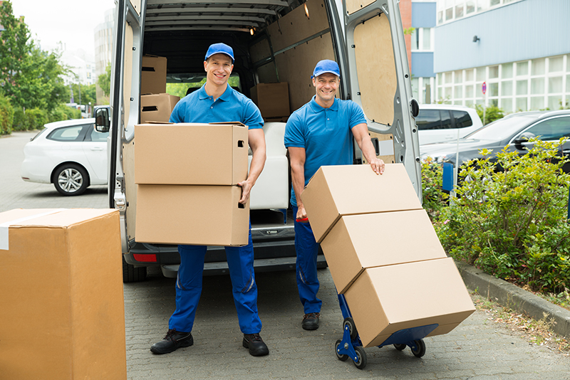 Two Happy Male Workers Loading Stack Of Cardboard Boxes In Truck