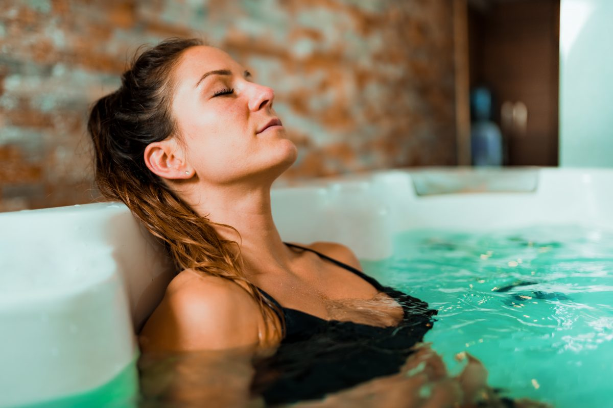 Beautiful Woman Enjoying Jacuzzi in Spa Center.
